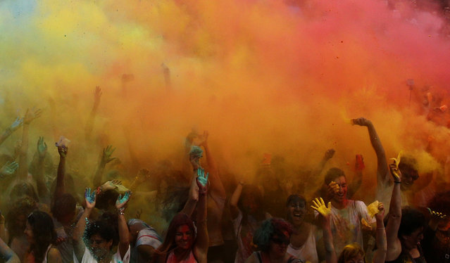 Participants throw special colored powders in the air during the Gay Pride parade at Moll de la Fusta in Barcelona, Spain, Saturday, July, 8, 2017. (Photo by Manu Fernandez/AP Photo)
