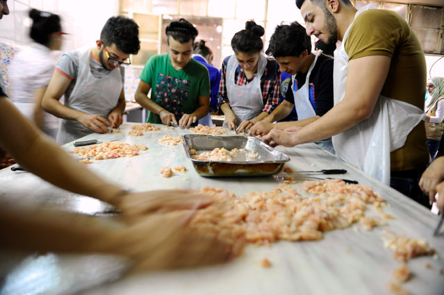 Youth, who are members of Saaed group, prepare food to be given out as Iftar meals for the poor and internally displaced Syrians during the month of Ramadan in Damascus, Syria June 18, 2016. (Photo by Omar Sanadiki/Reuters)