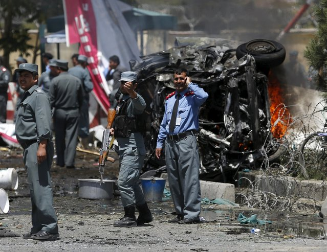 Policemen stand at the site of a car bomb blast at the entrance gate to the Kabul airport in Afghanistan August 10, 2015. A car bomb exploded near the entrance to Kabul airport and casualties are feared, officials said on Monday, days after series of suicide attacks in the Afghan capital killed dozens and wounded hundreds. (Photo by Ahmad Masood/Reuters)