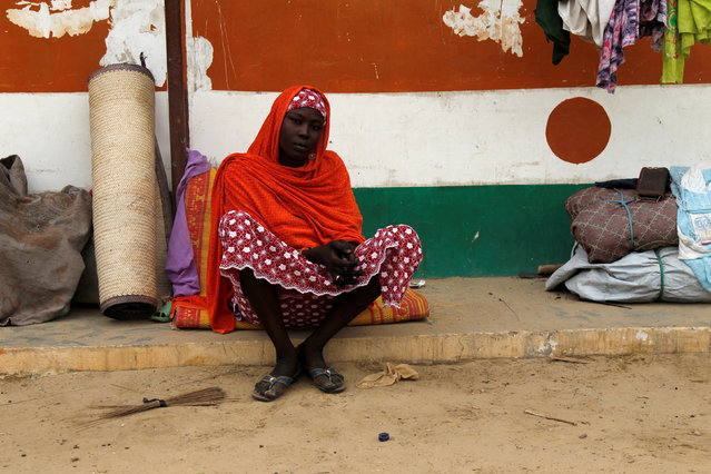 A displaced woman sits in front of a wall painted in the colors of Niger's national flag in an arena for traditional wrestling in the town of Diffa in southeastern Niger June 20, 2016. (Photo by Luc Gnago/Reuters)