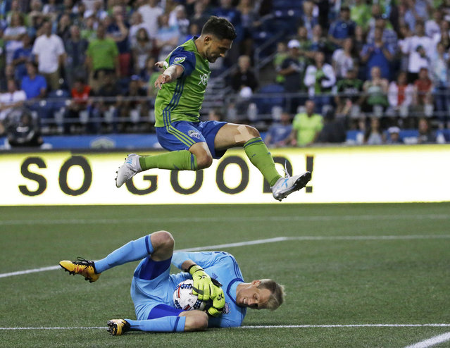 Seattle Sounders midfielder Cristian Roldan leaps over D.C. United goalkeeper Travis Worra during the second half of an MLS soccer match, Wednesday, July 19, 2017, in Seattle. The Sounders won 4-3. (Photo by Ted S. Warren/AP Photo)