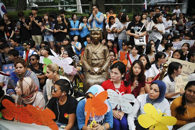 """Demonstrators sit around a """"comfort woman"""" statue during the weekly Wednesday protest demanding for an apology and compensation from the Japanese government in Seoul, South Korea, July 22, 2015. (Photo by Kim Kyung-Hoon/Reuters)"""