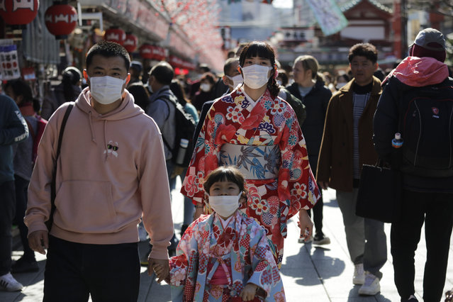 Tourists wear masks as they visit Sensoji Temple Thursday, January 30, 2020, in Tokyo. The country began evacuating Japanese citizens on Wednesday from the Chinese city Wuhan hardest-hit by the virus. (Photo by Jae C. Hong/AP Photo)