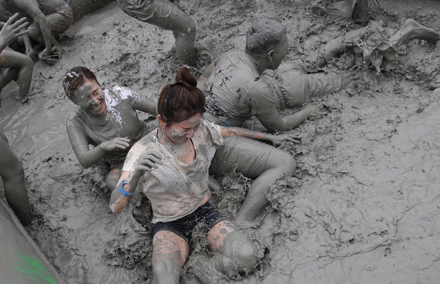 Festival goers wrestle in the mud during the annual Boryeong Mud Festival at Daecheon Beach on July 18, 2014 in Boryeong, South Korea. The mud, which is believed to have beneficial effects on the skin due to its mineral content, is sourced from mud flats near Boryeong and transported to the beach by truck. (Photo by Chung Sung-Jun/Getty Images)