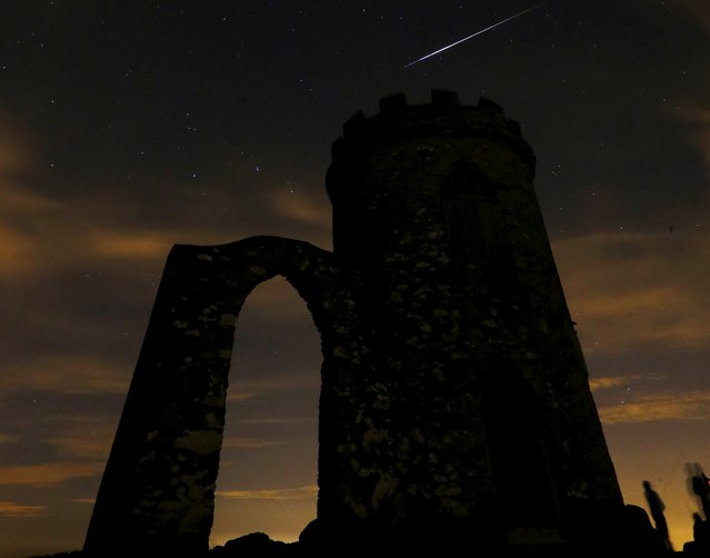 A meteor streaks across the sky during the Perseid meteor shower at Bradgate Park in Newtown Linford, Britain August 13, 2015. (Photo by Darren Staples/Reuters)