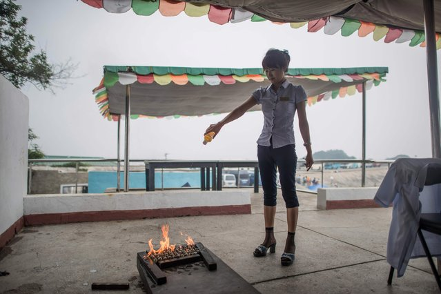 A photo taken on July 22, 2017 shows a hostess cooking clams using gasoline, at the West Sea Barrage beach outside the coastal city of Nampho, southwest of Pyongyang. (Photo by Ed Jones/AFP Photo)