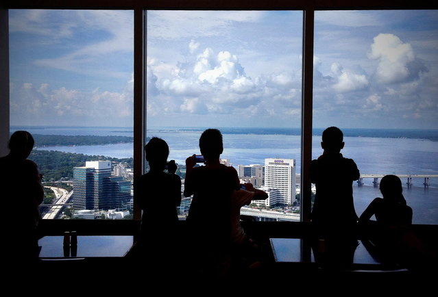 Photographers from the Museum of Contemporary Art Jacksonville photography camp take pictures from the 42nd floor of the Bank of America tower on Thursday, July 10, 2014, in Jacksonville, Fla. The young photographers are spending about half their time shooting pictures and the other half on the computer learning Photoshop techniques. Mario Peralta, their instructor, says the campers have been working on a variety of assignments including; collages, silhouettes, textures and multiple exposures. (Photo by Bruce Lipsky/AP Photo/Florida Times-Union)
