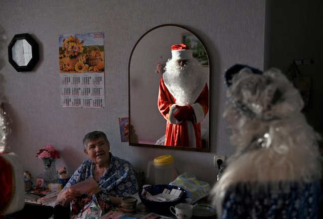 """Volunteers dressed as Father Frost and Snow Maiden present a gift to a resident of a nursing home on the occasion of the Christmas and New Year holidays, as part of the """"Old Age for Joy"""" charity project, in the village of Sosnovskoye in Omsk region, Russia on December 28, 2019. (Photo by Alexey Malgavko/Reuters)"""