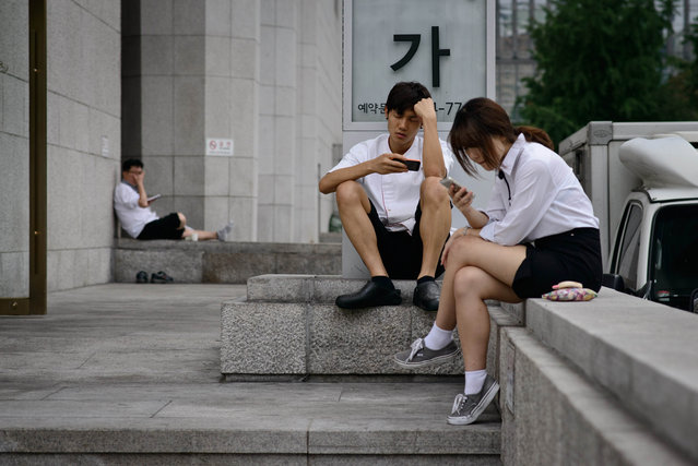 People look at their smartphones as they sit beside a street in central Seoul on July 29, 2014. South Korea logged a current account surplus of nearly 8.0 billion USD in June, slightly down from the May figure as import growth outpaced exports, the central Bank of Korea said on July 29. (Photo by Ed Jones/AFP Photo)