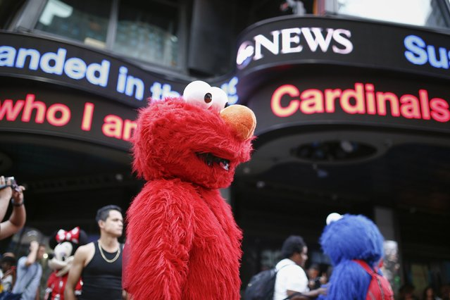 Jorge, an immigrant from Mexico, looks to make tips for photographs while dressed as the Sesame Street character Elmo in Times Square, New York July 30, 2014. (Photo by Eduardo Munoz/Reuters)