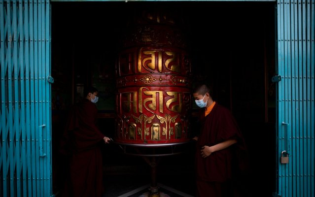 People wearing protective masks spin a prayer wheel during a mass prayer for the victims of coronavirus, at Boudhha stupa, also known as Boudhanath, in Kathmandu, Nepal, 15 February 2020. The event was organized by the famous Chokyi Nyima Rinpoche of Ka-Nying Monastery. Nepal has so far reported only one case of infection. The disease caused by the novel coronavirus (SARS-CoV-2) has been officially named COVID-19 by the World Health Organization (WHO). The outbreak, which originated in the Chinese city of Wuhan, has so far killed at least 1,526 people with over 67,000 infected worldwide, mostly in China. (Photo by Narendra Shrestha/EPA/EFE/Rex Features/Shutterstock)