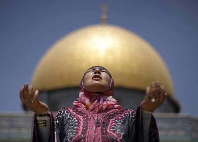 With the Dome of the Rock Mosque seen in the background, a Palestinian female Muslim worshipper prays during the first Friday prayers of the Muslim holy month of Ramadan, in the Al-Aqsa Mosque compound in Jerusalem's Old City, Friday, August 13, 2010. Muslims throughout the world are celebrating the holy month of Ramadan, where observants fast from dawn till dusk. (Photo by Muhammed Muheisen/AP Photo)