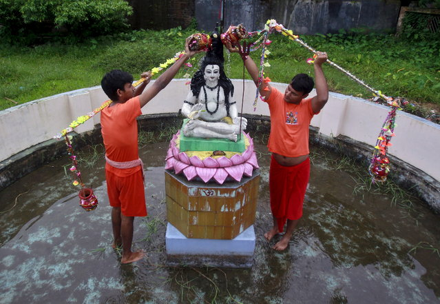 Kanwarias or devotees of the Hindu god Shiva offer prayers and pour sacred water on an idol of god Shiva outside a temple in Agartala, India, August 17, 2015. (Photo by Jayanta Dey/Reuters)