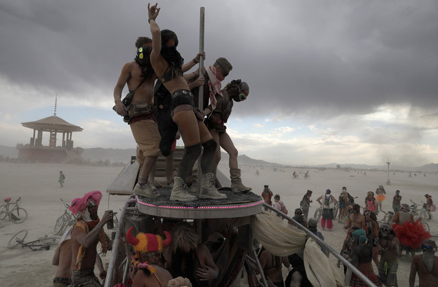 "Burning Man participants dance on and around ""The Penetrator"" art car near the effigy of ""The Man"" at the Burning Man arts and music festival in the Black Rock Desert of Nevada, U.S. August 30, 2017. (Photo by Jim Urquhart/Reuters)"