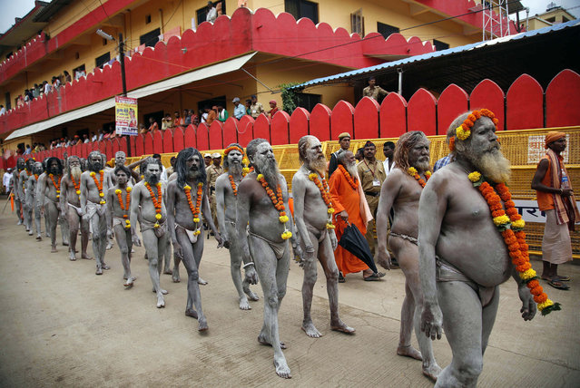 Naga sadhus, or naked Hindu holy men participate in a procession during Kumbh Mela, or Pitcher festival, at Trimbakeshwar in Nasik, India, Wednesday, August 26, 2015. Millions are expected to attend this year's two-month festival, which began in mid-July and runs until the end of September. (Photo by Rajanish Kakade/AP Photo)