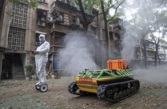 A volunteer operates a remote controlled disinfection robot to disinfect a residental area amid the COVID-19 coronavirus outbreak in Wuhan in China's central Hubei province on March 16, 2020. China tightened quarantine measures for international arrivals on March 16 as the country worries about a rise in imported cases of the deadly coronavirus and anger rages online at how Europe and the United States are handling the pandemic. (Photo by AFP Photo/China Stringer Network)
