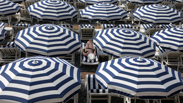 A tourist enjoys the sun on a beach covered with umbrellas on the Promenade Des Anglais during a sunny summer day in Nice, France, July 11, 2017. (Photo by Eric Gaillard/Reuters)