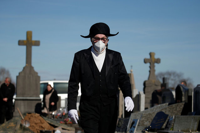 A member of the Charitable Brotherhood of Saint-Eloi de Bethune, which first formed during the plague 800 years ago, wears a protective face mask as he walks in the cemetery during a burial ceremony in Bethune, France, March 18, 2020. Funeral gatherings are restricted because of the coronavirus disease (COVID-19) outbreak. (Photo by Pascal Rossignol/Reuters)