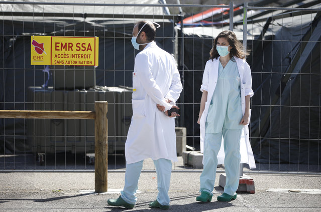 Civil medical staff walk past the military field hospital built in Mulhouse, eastern France, Monday March 23, 2020. The Grand Est region is now the epicenter of the outbreak in France, which has buried the third most virus victims in Europe, after Italy and Spain. (Photo by Jean-Francois Badias/AP Photo)