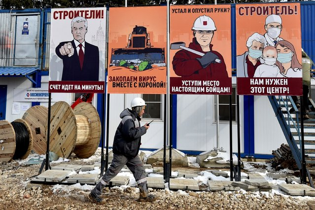 A worker walks past billboards on the construction site of a new Covid-19 Hospital for patients infected with the novel coronavirus, outside Moscow, on April 1, 2020, as the city is under lockdown in order to stop the spread of the COVID-19 outbreak. (Photo by Vasily Maximov/AFP Photo)