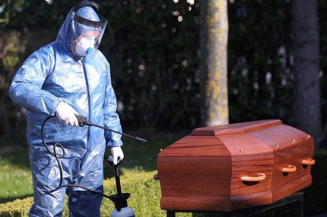 A mortuary worker sprays disinfectant on a coffin of a person who died of the coronavirus disease (COVID-19), near the city of Charleroi, Belgium on April 7, 2020. (Photo by Yves Herman/Reuters)