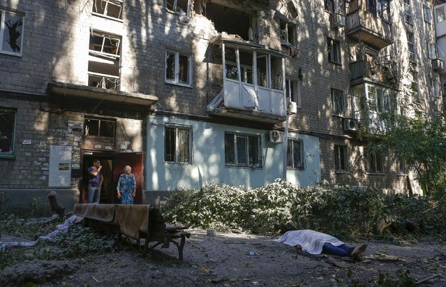Local residents stand at a damaged apartment block near the body of a victim killed by what locals say was recent shelling by Ukrainian forces in Donetsk August 23, 2014. (Photo by Maxim Shemetov/Reuters)
