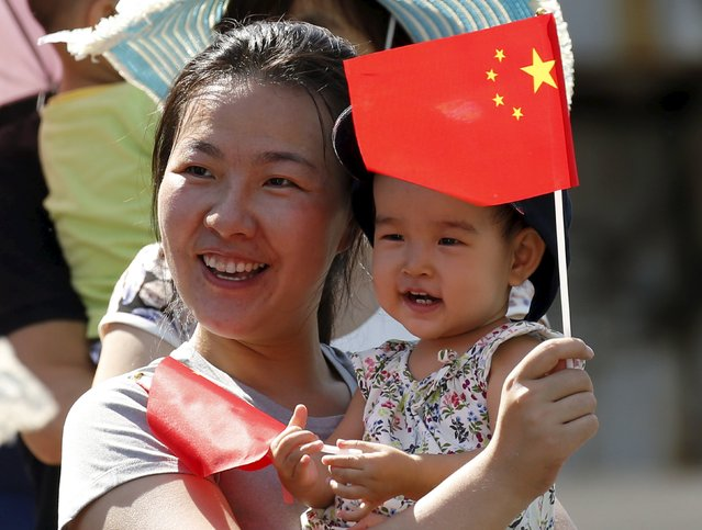 A woman and her baby wait on the street for the performance of military helicopters and planes during the military parade marking the 70th anniversary of the end of World War Two, in Beijing, China, September 3, 2015. (Photo by Kim Kyung-Hoon/Reuters)