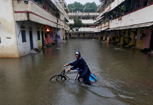 A delivery boy pushes his bicycle through a water-logged street after heavy rains at a residential colony in Mumbai, India September 20, 2017. (Photo by Shailesh Andrade/Reuters)