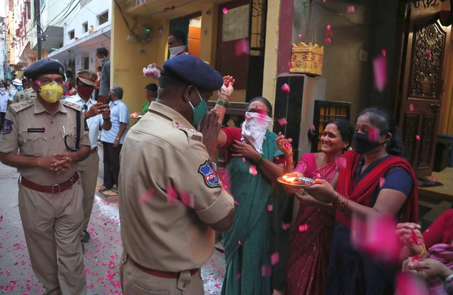Indians shower rose petals and worship policemen as a mark of respecting frontline workers in the fight against COVID-19 during a lockdown to control the spread of the new coronavirus in Hyderabad, India, Sunday, April 19, 2020. (Photo by Mahesh Kumar A./AP Photo)