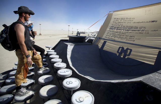 "Matt Steele (L) and Soroya Rowley read the poem on the Blunderwood Portable art installation during the Burning Man ""Carnival of Mirrors"" arts and music festival in the Black Rock Desert of Nevada, September 4, 2015. (Photo by Jim Urquhart/Reuters)"