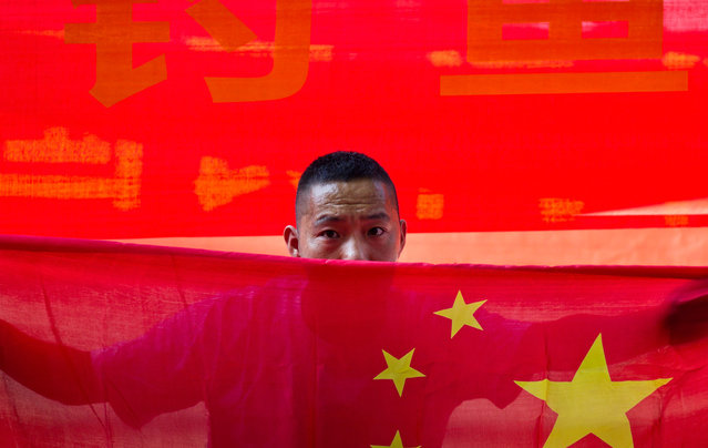 A Chinese man holds a national flag during a protest outside the Japanese Embassy in Beijing, on August 15, 2012. (Photo by Andy Wong/AP Photo)