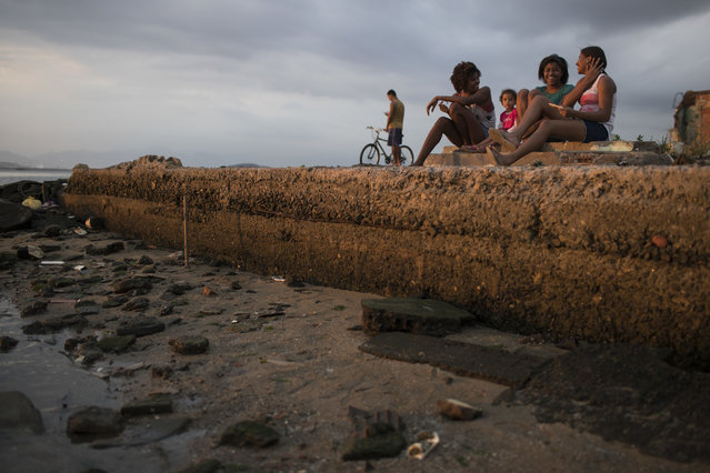 Girls chat as they sit near the shores of of Guanabara Bay, the venue for sailing at the 2016 Summer Olympic Games, in Rio de Janeiro, Brazil, Saturday, July 30, 2016. The international sporting event is fast approaching, with the opening ceremony less than a week away. (Photo by Felipe Dana/AP Photo)