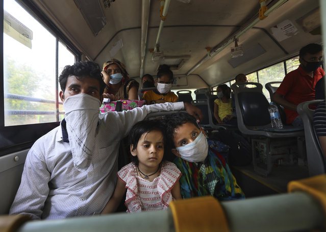A migrant family from another state trying to return to their villages waits in bus to be transported to a railway station in New Delhi, India, Monday, May 18, 2020. India has recorded its biggest single-day surge in new cases of coronavirus. The surge in infections comes a day after the federal government extended a nationwide lockdown to May 31 but eased some restrictions to restore economic activity and gave states more control in deciding the nature of the lockdown. (Photo by Manish Swarup/AP Photo)
