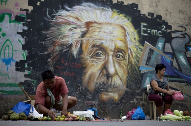 A vendor arranges vegetables for sale in front of street art featuring Albert Einstein in Manila on September 18, 2014. The Philippine economy rebounded to post 6.4-percent growth in the second quarter and regain its status as one of the strongest in Asia, authorities said in August. (Photo by Noel Celis/AFP Photo)