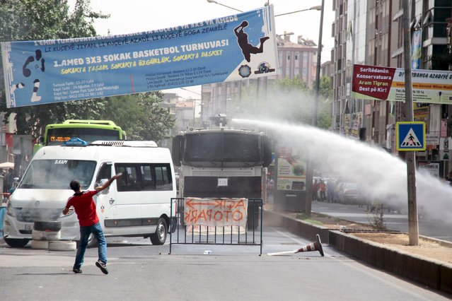 Riot police use water cannon to disperse stone throwing protesters in the Kurdish dominated southeastern city of Diyarbakir, Turkey, September 13, 2015. Kurdish militants on Sunday killed two police officers when they bombed a checkpoint in Sirnak in southeast Turkey and a curfew was imposed in central Diyarbakir, the region's largest city, after clashes there, security sources and officials said. (Photo by Sertac Kayar/Reuters)