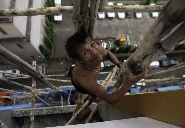 A man climbs a scaffolding at a construction site in Yangon, Myanmar October 16, 2012. (Photo by Soe Zeya Tun/Reuters)
