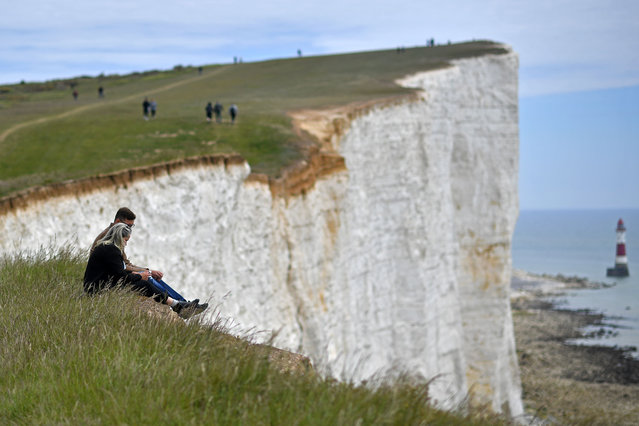 "A couple sit on the cliff-edge above the lighthouse at Beachy Head near Eastbourne on the south coast of England on May 17, 2020, following an easing of lockdown rules in England during the novel coronavirus COVID-19 pandemic. People are being asked to ""think carefully"" before visiting national parks and beaches on the first weekend since coronavirus lockdown measures were partially eased in England. (Photo by Ben Stansall/AFP Photo)"