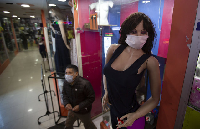 A mannequin wearing a face mask stands at the entrance of a women's clothing store in La Paz, Bolivia, Monday, June 1, 2020. After more than two months of quarantine to curb the spread of the new coronavirus the government authorized the restart of public transport and several industrial and commercial activities. (Photo by Juan Karita/AP Photo)