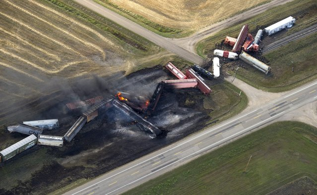 A Canadian National Railway Company freight train carrying dangerous goods derailed and caught fire near the town of Wadena, Saskatchewan, Tuesday, October 7, 2014. The Saskatchewan government said the derailment happened near the small community of Clair, which is being evacuated. (Photo by Liam Richards/AP Photo/The Canadian Press)