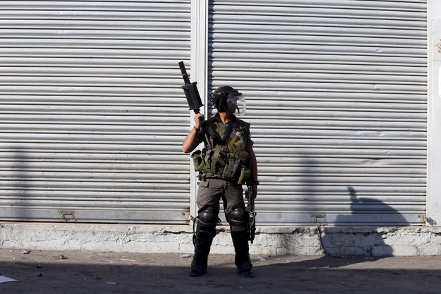 Israeli border policeman stands on a street during clashes with Palestinian stone-throwers in the Shuafat refugee camp near Jerusalem September 18, 2015. (Photo by Ammar Awad/Reuters)