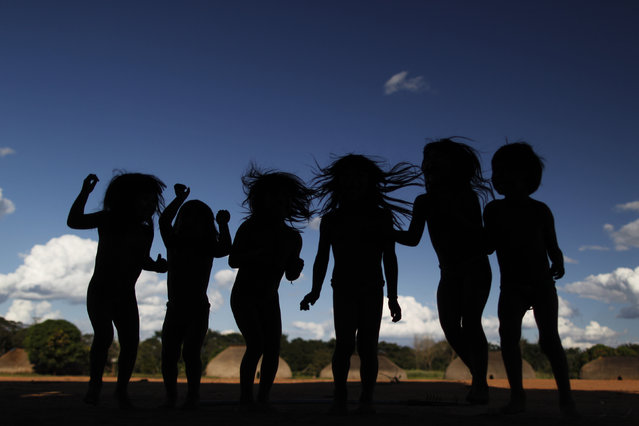 """Yawalapiti children play during the preparations for the celebration of """"quarup"""", a ritual held to honor in death a person of great importance to them, in the Xingu National Park, Mato Grosso State, May 7, 2012. (Photo by Ueslei Marcelino/Reuters)"""