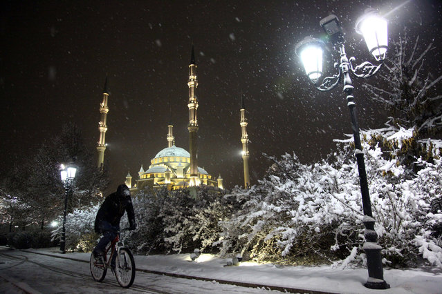 A man rides a bicycle during a snowfall, as the main Mosque is illuminated for New Year celebrations in downtown Grozny, the capital of Chechnya, Russia, Friday, December 8, 2017. (Photo by Musa Sadulayev/AP Photo)