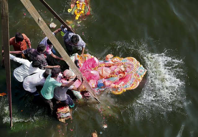 Devotees immerse an idol of the Hindu god Ganesh, the deity of prosperity, into the Sabarmati river on the last day of the 10-day-long Ganesh Chaturthi festival in Ahmedabad, India, September 27, 2015. (Photo by Amit Dave/Reuters)