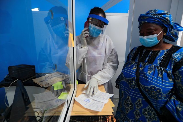 A healthcare worker wearing protective gear checks a document of a woman as she waits to be tested for the coronavirus disease (COVID-19) at an Institute for Health Research, Epidemiological Surveillance and Training (IRESSEF) testing center in Dakar, Senegal on July 24, 2020. (Photo by Zohra Bensemra/Reuters)