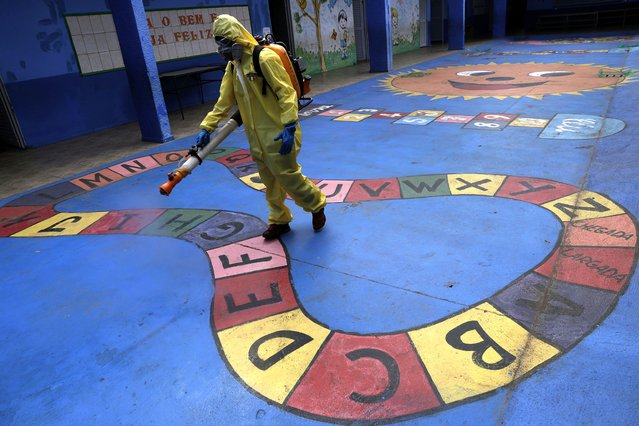 A government employee disinfects a public school as a measure against the spread of the new coronavirus, in the Taguatinga neighborhood of Brasilia, Brazil, Tuesday, July 28, 2020. The local government has began preparing for the safereopening of schools in mid-August, asrestrictionsrelated to the COVID-19 lockdownare eased. (Photo by Eraldo Peres/AP Photo)