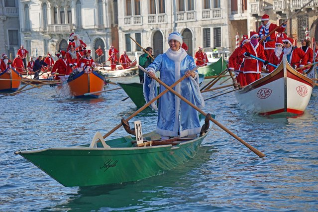 People wearing Santa Claus costumes row on Canal Grande in Venice, Italy, Sunday, December 17 2017. Almost a hundred traditional rowing boats, of various kinds and sizes, for about two hundred rowers, gave life to the traditional water procession of the Santa Claus, parading along the Grand Canal. (Photo by Andrea Merola/ANSA via AP Photo)