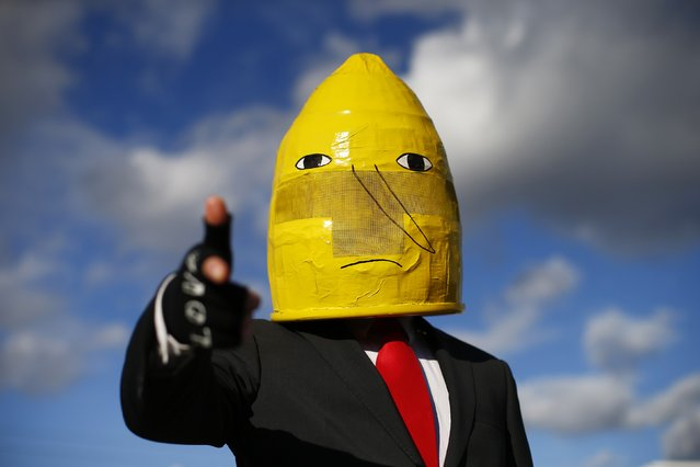 "A man poses as ""Lemongrab"" from Adventure Time outside the MCM Comic Con at the Excel Centre in East London, October 25, 2014. (Photo by Andrew Winning/Reuters)"