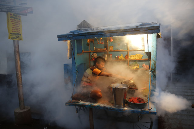 A man who sells chewable tobacco covers his items as a municipal worker fumigates to prevent mosquitoes from breeding in Lucknow, India, Tuesday, September 22, 2015. Dengue outbreaks are reported every year after the monsoon season that runs from June to September. Many people have died from the mosquito-borne disease in the country's capital New Delhi this year. (Photo by Rajesh Kumar Singh/AP Photo)