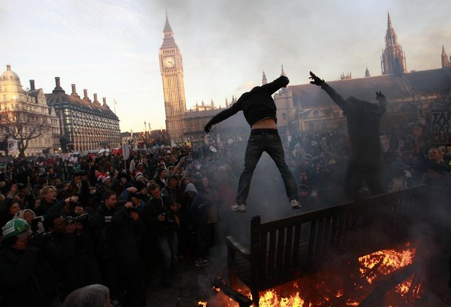 Demonstrators jump off burning park benches during a protest outside the Houses of Parliament in Westminster, central London December 9, 2010. Britain's parliament approved plans to increase fees paid by university students despite a rebellion by members of the coalition government. Protesters had earlier clashed with police outside parliament in central London during the debate. (Photo by Andrew Winning/Reuters)