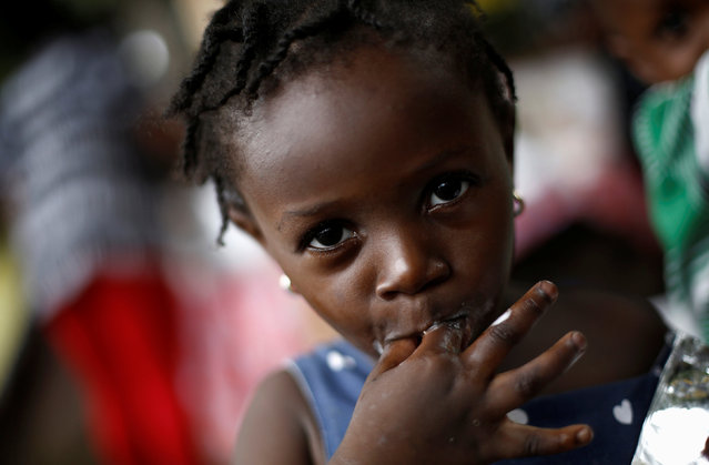 An African migrant child eats ice cream at makeshift camp at the border between Costa Rica and Nicaragua, in Penas Blancas, Costa Rica, September 7, 2016. (Photo by Juan Carlos Ulate/Reuters)
